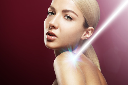 34674281 - georgeous woman with a ray of light or laser on her shoulder